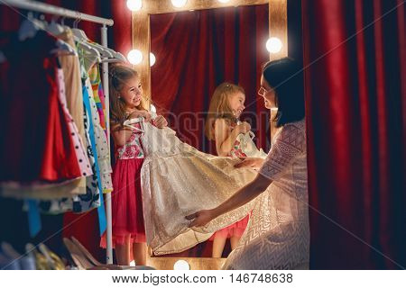 Cute little fashionista. Young mother and her daughter child girl try on outfits and look at mirror.