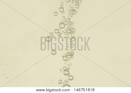 Beautiful golden air bubbles flowing over a blurred background