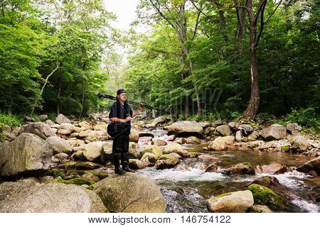 Photographer with camera and tripod travels across mountain river