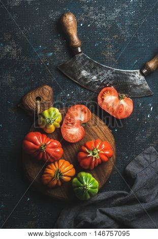 Fresh colorful ripe heirloom tomatoes on wooden board, herb chopper knife for cooking over grunge dark plywood background, top view. Harvest vegetable cooking conception.
