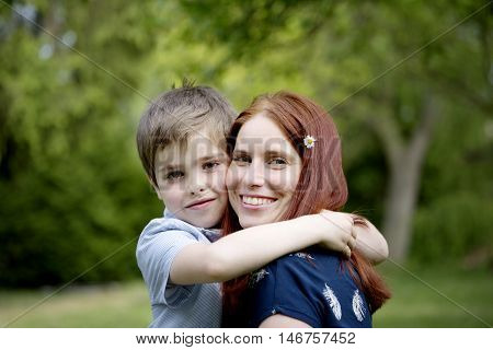 Nice white boy with beautiful young woman on spring sunny garden. Portrait of boy with mother. Happy family in sunny day. Mother and sun spend leisure time activities in nature. Plaing with flowers.