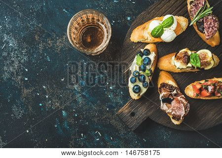Italian crostini with various toppings on round wooden board and glass of rose wine over black plywood background, top view, copy space, horizontal composition