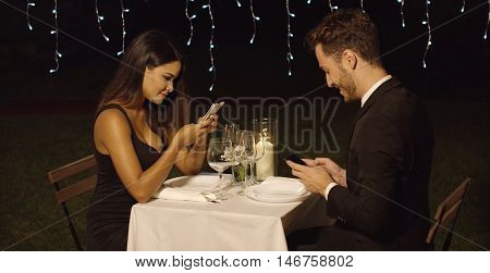 Young couple checking their mobiles during dinner