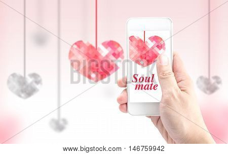 Hand holding smartphone with pink polygon heart shape and Soulmate word on screen on blur heart background Love concept.