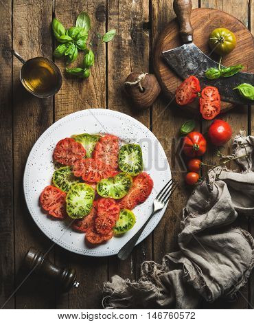 Heirloom tomato salad with olive oil and basil over old rustic wooden background, top view, vertical composition