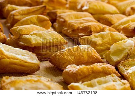 Rows of yellow puffs. Pastry on light wooden board. Income of bakery is growing. Sweet airy dough.