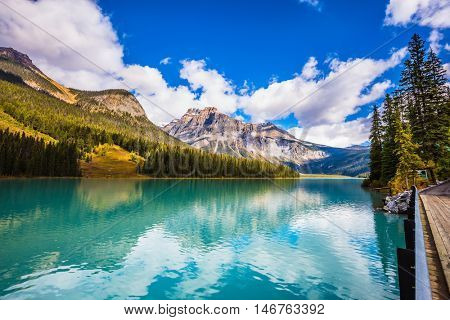 The smooth turquoise water in the wooded mountains. Sunny day in autumn. The concept of eco-tourism and active recreation. Charming mountain Emerald lake. Yoho National Park, Canada poster