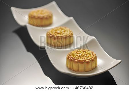 Three traditional mooncakes on a white plate
