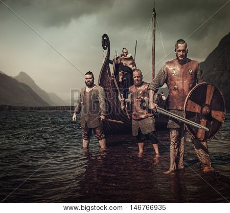 Armed, mad vikings warriors, standing on the seashore with Drakkar on the background.