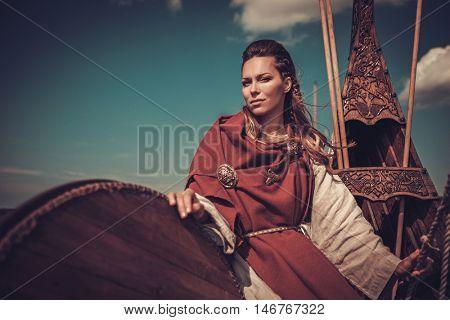 Confident viking woman with shield on Drakkar.