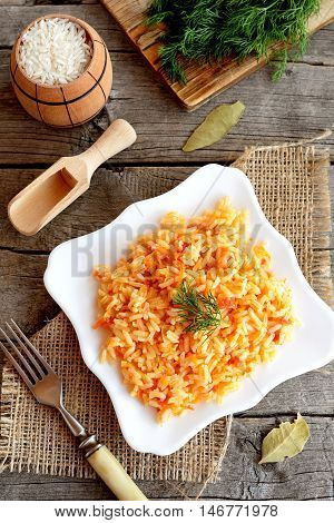 Vegetable risotto on a plate, fork, green dill, cutting board on old wooden background. Rice cooked with tomatoes, carrots, garlic and spices. Easy vegetarian risotto recipe