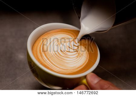 Barista creating latte art on long coffee with milk. Latte art in coffee mug. Barman pouring fresh coffee