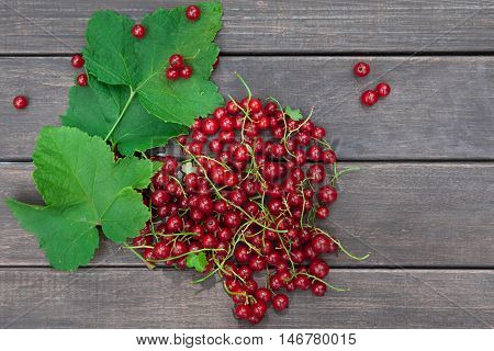 Fresh ripe red currants heap on rustic wood background. Natural organic berries with green leaves scattered on weathered grey wooden table, new berry harvest top view with copy space