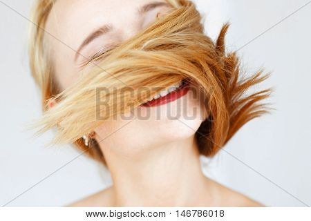Happy red haired woman playing with her hair. Portrait of cheerful carroty girl with locks on face. Good hairdresser, health and care concept