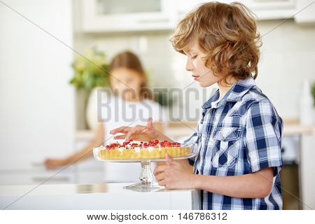Boy nibbling from fresh fruit cake with red currants in the kitchen