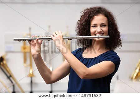 Beautiful girl playing flute in music shop