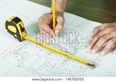 repair, building and home concept - close up of male hands making changes to blueprint