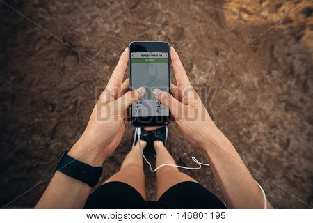 Woman checking the summary of her run on smartphone. POV shot of woman runner using a fitness app on her cellphone.