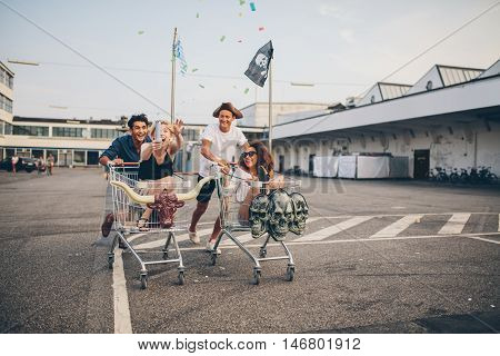 Multiracial group of friends racing with shopping cart. Young people racing with shopping trolleys on road.