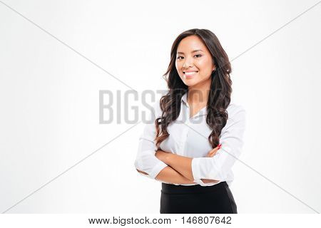 Portrait of smiling pretty young asian businesswoman standing with arms crossed over white background