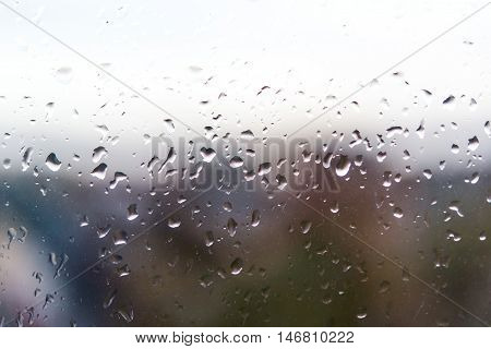 Drops of rain on the train window with tree in background.