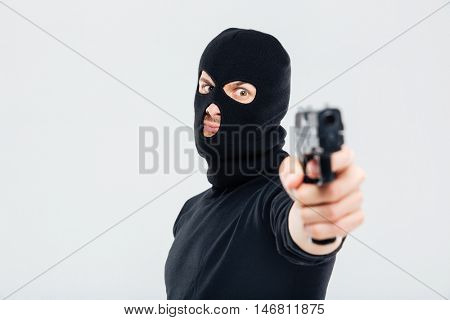 Closeup of man in balaclava standing and aiming with gun
