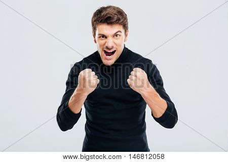 Mad crazy young man threatening with fists and shouting