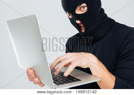 Closeup of criminal man in balaclava using laptop