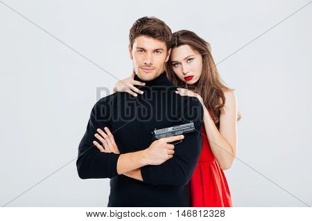 Portrait of beautiful stylish young couple with gun