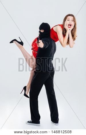 Man in balaclava stealing young woman and pointing gun on you