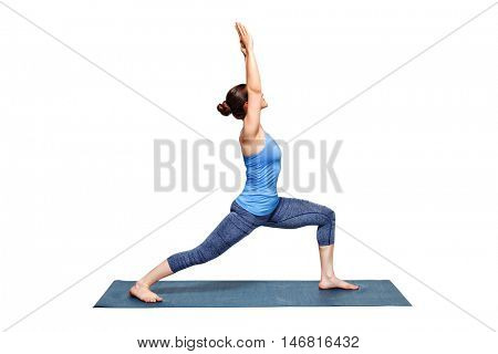 Beautiful sporty fit woman practices Ashtanga Vinyasa Yoga asana Virabhadrasana 1 - warrior pose 1 isolated on white