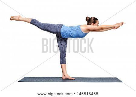 Beautiful sporty fit woman practices yoga asana Virabhadrasana 3 - warrior 3 pose isolated on white