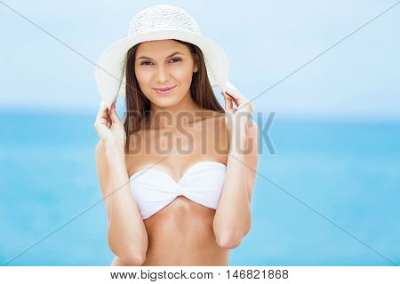 Beach woman happy and playful smiling laughing playful and cheerful in summer sun. Beautiful multiracial Asian Chinese / Caucasian woman wearing white beach hat and bikini