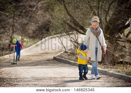 Happy family walking in the park. Mother with two children in the park on a sunny spring day. Woman with cute toddler boy and a boy on a skate. Outdoors.