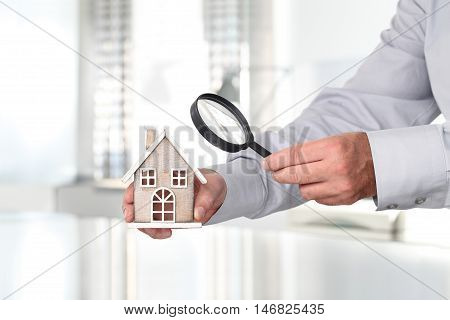 Hands with house and magnifying glass search home concept