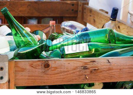 green empty glass wine glass bottels on a heap in wooden box