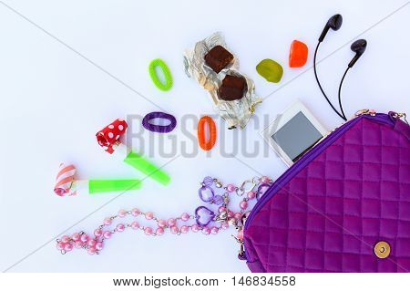 Children's handbag and accessories: cell phone, whistle, hair bands, candy, beads, headphones on white background.  Top view.