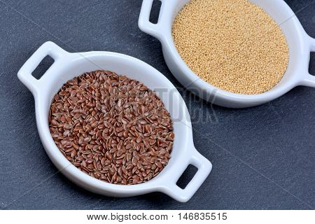 Flaxseeds with amaranth in a ceramic bowls on slate