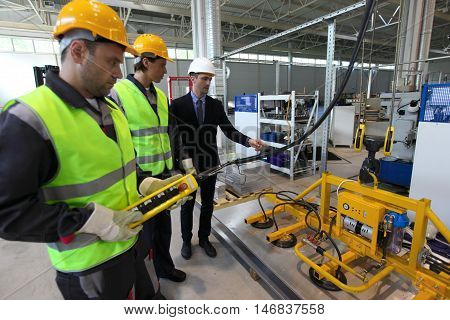 Manager and workers near metal sheet lifting device at factory