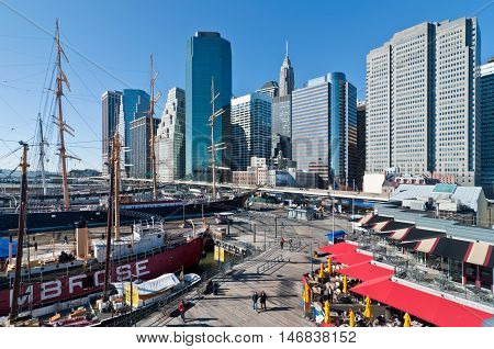 New York City USA - November 18 2011: People walk in Landmark seaport located next to Wall Street and financial center on a sunny day at November 18 2011 NYC. The port is a designated historic district containing the largest concentration of 19th century