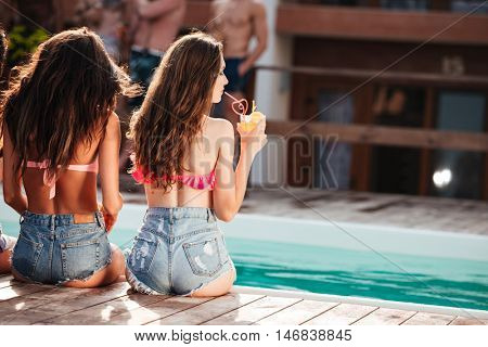 Cute young women with long hair in jeans shorts sitting near swimming pool and drinking juice