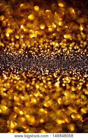 Dark Gold Festive blur background. Abstract night twinkled bright background with bokeh defocused golden lights. Christmas blurry boke lights