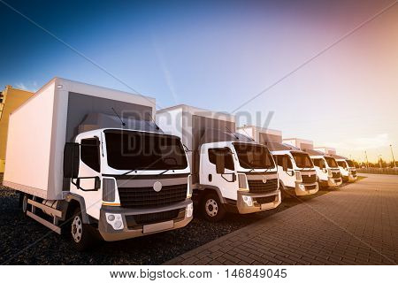Fleet of commercial delivery trucks on cargo parking. Generic, brandless vehicle design. 3D rendering
