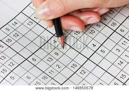Woman hand holding a pencil and solves crossword sudoku. Popular puzzle game with numbers.