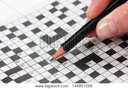 Woman hand holding a pencil and solves crossword puzzle.