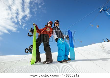 Friends snowboarders stands on the slope of mountain with snowboards
