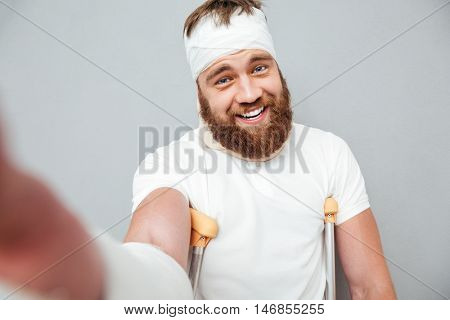 Cheerful young man with crutches taking selfie over white background