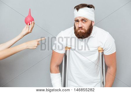 Depressed sad bandaged injured man going to have an enema procedure over gray background