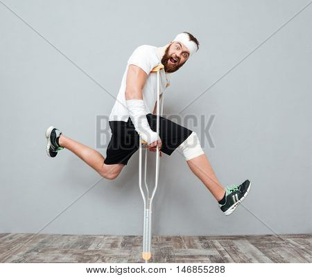 Freaky crazy young man jumping with crutches and shouting over gray background