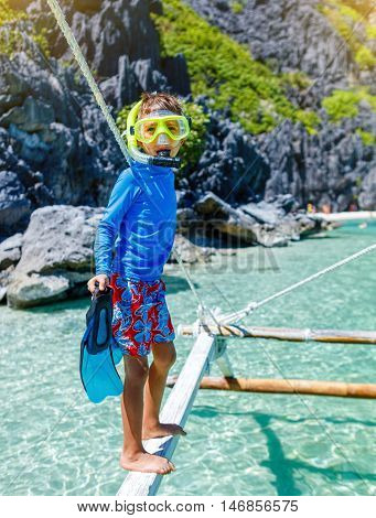Joyful boy on the tropical beach ready for scuba diving.